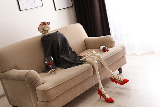 Skeleton in dress with wine sitting on sofa at home