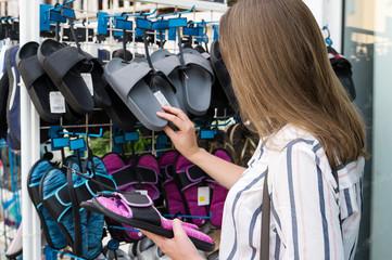 Pretty woman choosing flip-flops in shop on vacation.