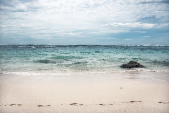 Beach with footprints on sand sea surf waves turquoise water blue dramatic sky on horizon landscape