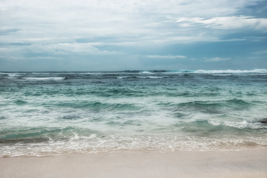 Sea beach surf waves turquoise water blue dramatic overcast sky landscape