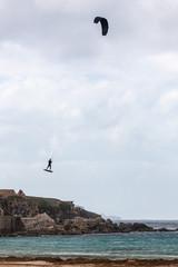 Man practicing kitesurfing on the waves of Tarifa near the Isla de Las Palomas, which separates Mediterranean and the Atlantic Ocean, Spain.