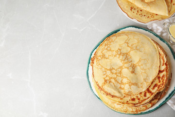 Stack of fresh thin pancakes on light grey marble table. Space for text