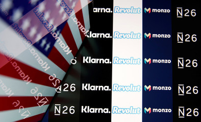 The N26, Monzo, Revolut and Klarna logos are reflected in a laptop screen while the U.S. flag is displayed, in this illustration