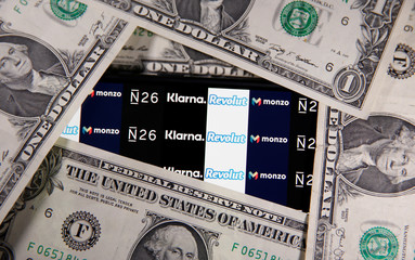 The N26, Monzo, Revolut and Klarna logos are displayed behind U.S. dollar banknotes in this illustration