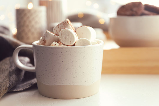 Cup of delicious hot cocoa with marshmallows on white table, closeup. Winter drink