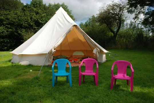 Bell tent in a field with 3 plastic chairs