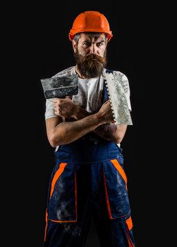 Bearded builder isolated on black background. Bearded man worker with beard, building helmet, hard hat. Plastering tools. Tool, trowel, handyman, man builder. Mason tools, builder