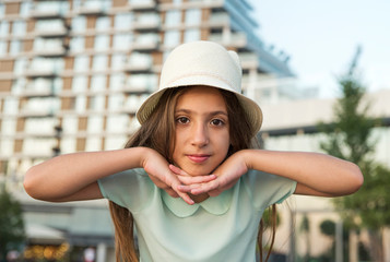 Outdoor portrait of a cute funny girl with hat