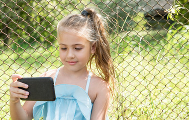 Cute little girl sit in the park and looking at smartphone