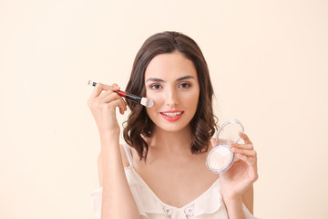 Wall Mural - Beautiful young woman applying makeup on light background