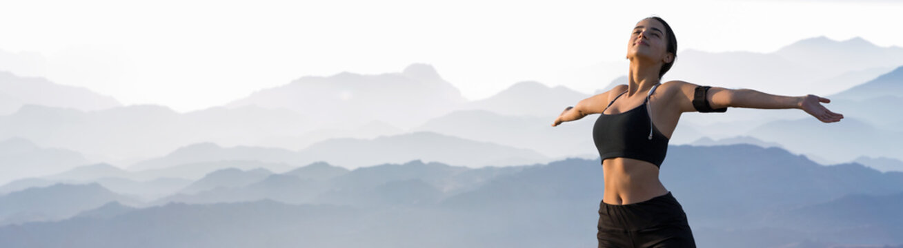 A thin athletic girl takes a break between classes on the background of mountains in the early morning, enjoys silence and freedom.