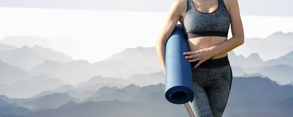 In de dag Ontspanning A young slim athletic girl in sportswear performs a set of exercises on the background of mountains. Stands with a yoga mat.