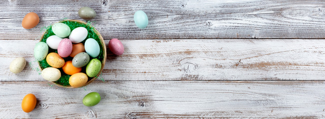 Happy Easter holiday with basket filled of colorful eggs on white weathered wood. Overhead view with plenty of copy space