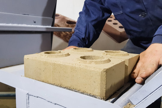 Brick making by hand pressing in clamping mechanism.