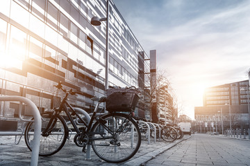 Aluminium Prints Bicycle Bike parked near modern apartment residential buiding or college campus at downtown of european city street. Eco-friendly transport and healthy active lifestyle concept. Sustainable work commute