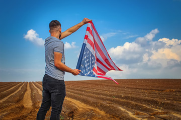 American patriot with USA flag on a plowed field, American farm. Guy holding usa flag. Photos on the topic federal holiday: Independence Day United States