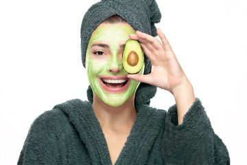 Beautiful young woman with avocado facial mask. Skin care beauty treatment