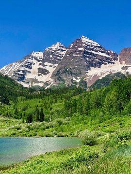 Maroon Bells mountain range turquoise lake and evergreen pine trees and aspens at Maroon Bell Scenic Recreation Area, near Aspen Highlands Ski Area, Colorado Rockies