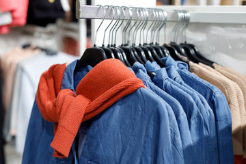 Hangers with denim shirts and sweaters in the sales area. Sale of casual clothing in the shopping center. Modern fashion store