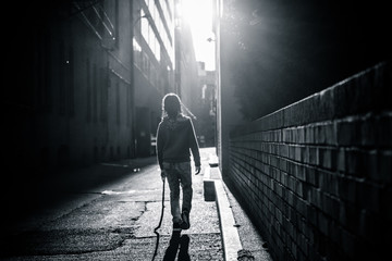 A little girl in beaded braids walks down an alley into the sun. Fotomurales
