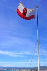 The flag of Gibraltar floating on a mast
