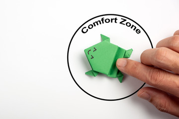 Step out from the comfort zone concept. A dark green origami frog is ready to jump out of the comfort zone.