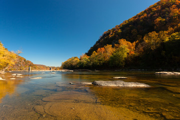 The crystal clear Water of the  Potomac River in Harper's Ferry, West Virginia, on a sunny Day with colorful Foliage on Trees