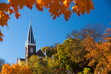 Church Steeple on a sunny Day in Fall with blue Sky and colorful Foliage on Trees