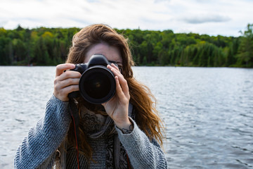 Young woman traveler clicking pictures using DSLR camera while in lake of Northern Quebec in Canada with fur and spruce tress in background