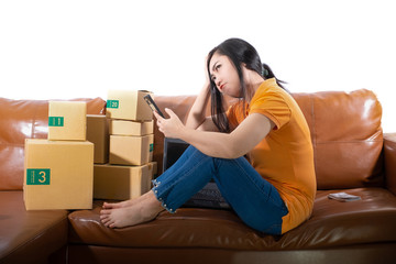 Portrait Bored young woman is sitting on the sofa at her room, Women used  mobile phone on white background, A lady is bored because sales dropped from sales target concept
