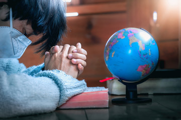 Close up hands of christian in mask praying for globe, stop Disease Virus and War in the world, christian praying concept.