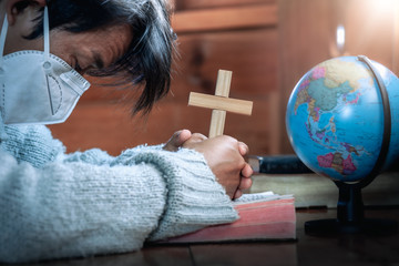 Christian man in mask holding cross and praying for globe, stop Disease Virus and War in the world, christian praying concept.