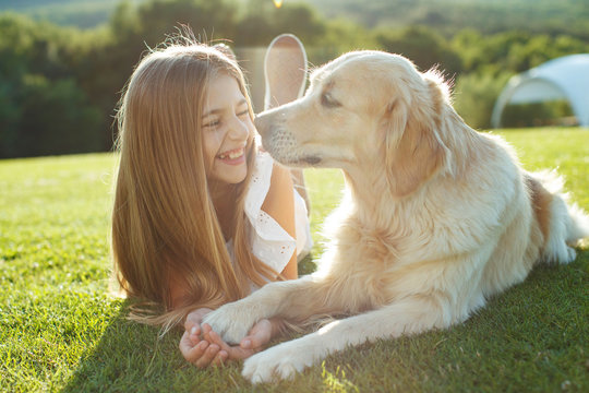 A child plays with a dog.