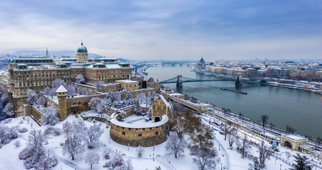 Budapest, Hungary - Aerial panoramic view of the snowy Buda Castle Royal Palace from above with the Szechenyi Chain Bridge and Parliament of Hungary at winter time