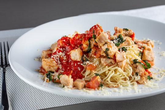 A view of a plate of chicken angel hair pasta in a restaurant or kitchen setting.