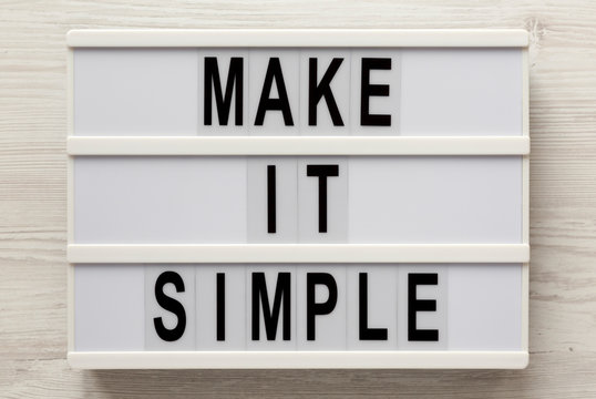 'Make it simple' words on a lightbox on a white wooden background, top view. Overhead, from above, flat lay. Close-up.