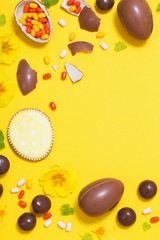 Easter yellow background with chocolatte eggs,    candy and spri