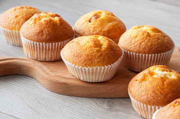 Fresh homemade delicious muffins are taken out of the oven and they cool on the kitchen table. Sweet dessert.