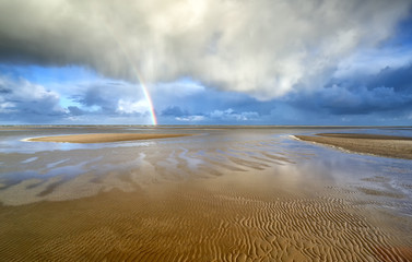 rainbow and dramatic storm cloud over sea