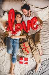 Overhead view of young lovely happy caucasian couple in bed holding red inflated word love with present boxes beside them, top view. Saint Valentines day greeting card
