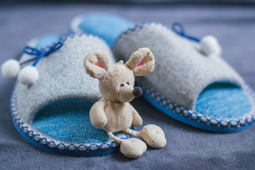 A toy mouse sits on slippers with pompons standing on a fluffy carpet. Home women's or children's clothing and shoes. The concept of home warmth and comfort. Selective focus.