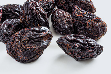 Shriveled and cracked prunes on a light gray background