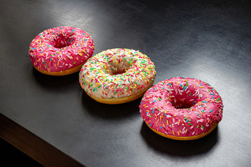 Traditional glazed doughnuts on a dark background