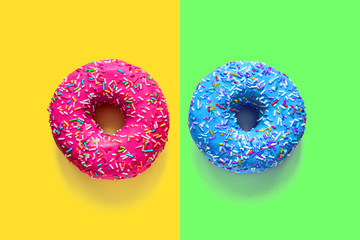 Two glazed doughnuts pink and blue on multicolored backgrounds