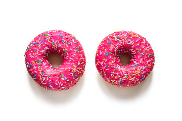 Two pink glazed doughnuts on a white background