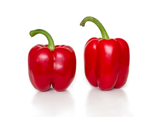 Two red bell peppers with green cuttings on a white background