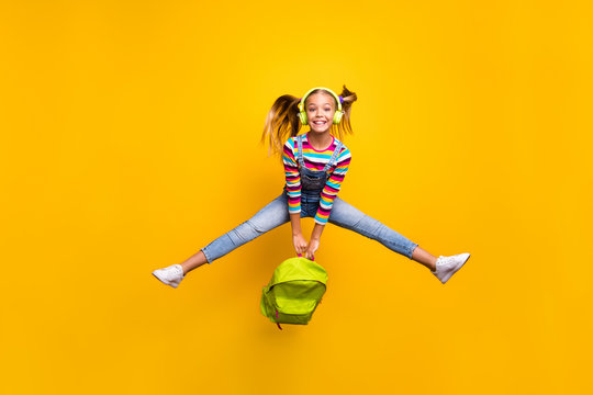 Full length photo energetic crazy schoolkid hold backpack bags enjoy school lessons listen songs wear denim jeans striped sweater footwear isolated bright shine yellow color background
