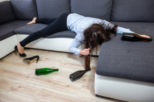Drunk woman lying on the sofa with kind of wine bottles, alcoholism concept, alcohol addiction