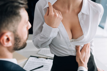 Fototapeta cropped view of businessman hugging sexy secretary with big breast in office obraz