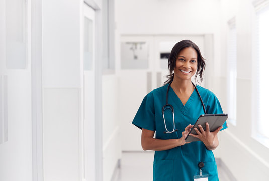 Portrait Of Smiling Female Doctor Wearing Scrubs In Hospital Corridor Holding Digital Tablet